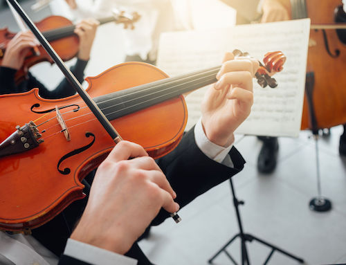 46506706 - confident violinist playing his instrument and reading a music sheet, classical music symphony orchestra performing on background